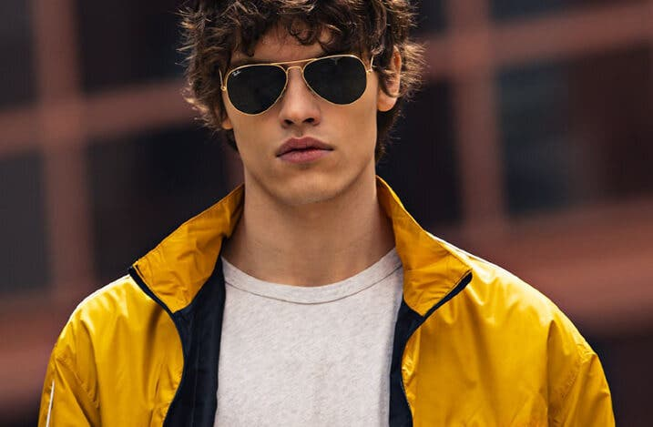 young man wearing ray ban rb3025 aviator sunglasses in arista gold with g-15 green lenses