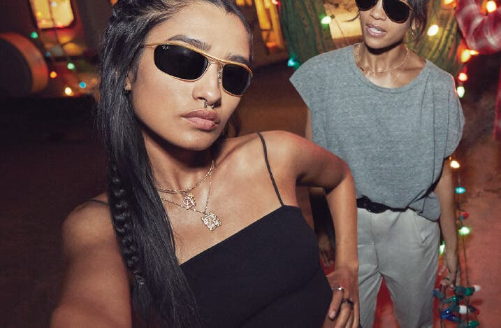young woman wearing ray ban sunglasses rb3119 olympian in gold with g-15 lenses and another woman wearing ray ban rb3025 aviator in gold with g-15 lenses